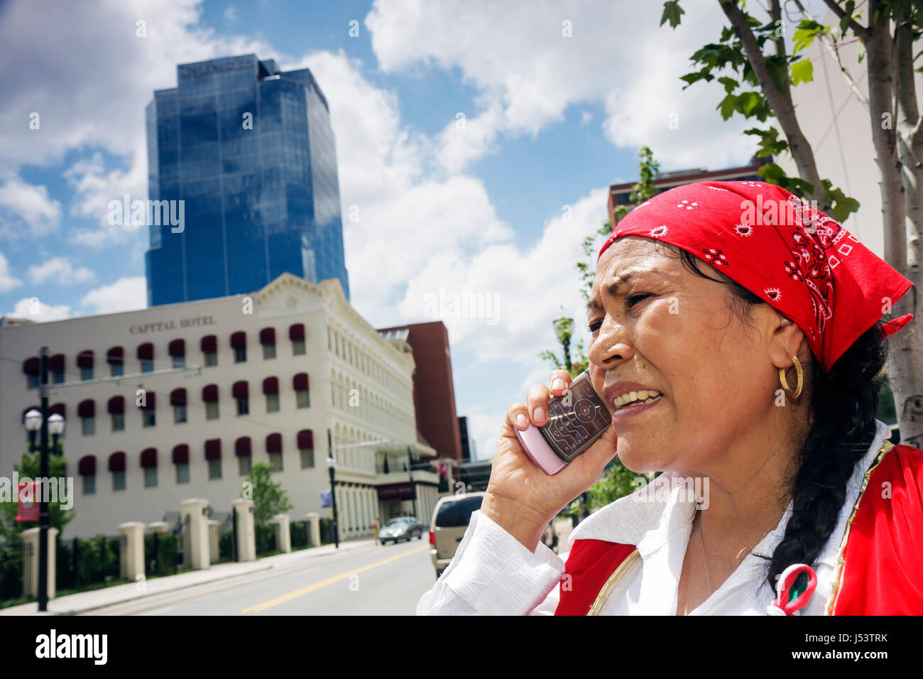 Little Rock Arkansas Markham Street Mexican performer mobile cell phone Hispanic woman costume red bandana speak - Stock Image
