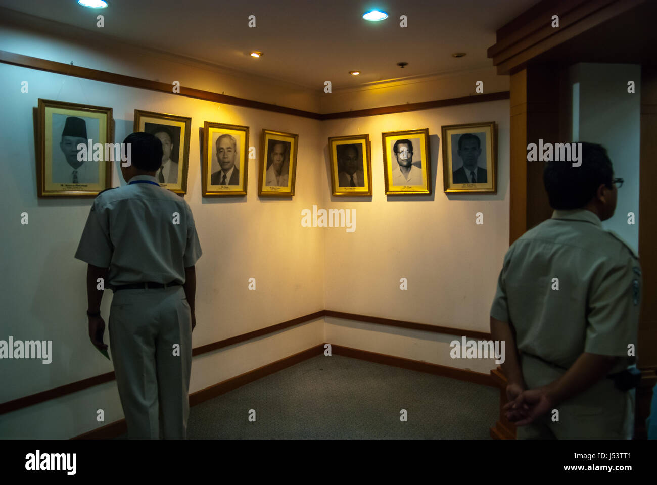 Government officers paying attention to the portraits of previous Indonesian Health Ministers displayed in the ministry's - Stock Image