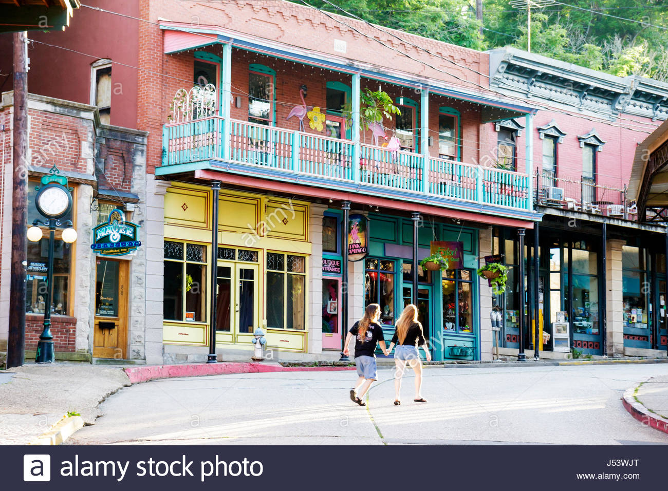 Arkansas Eureka Springs historic renovated shops couple man woman balcony store fronts short pants Stock Photo