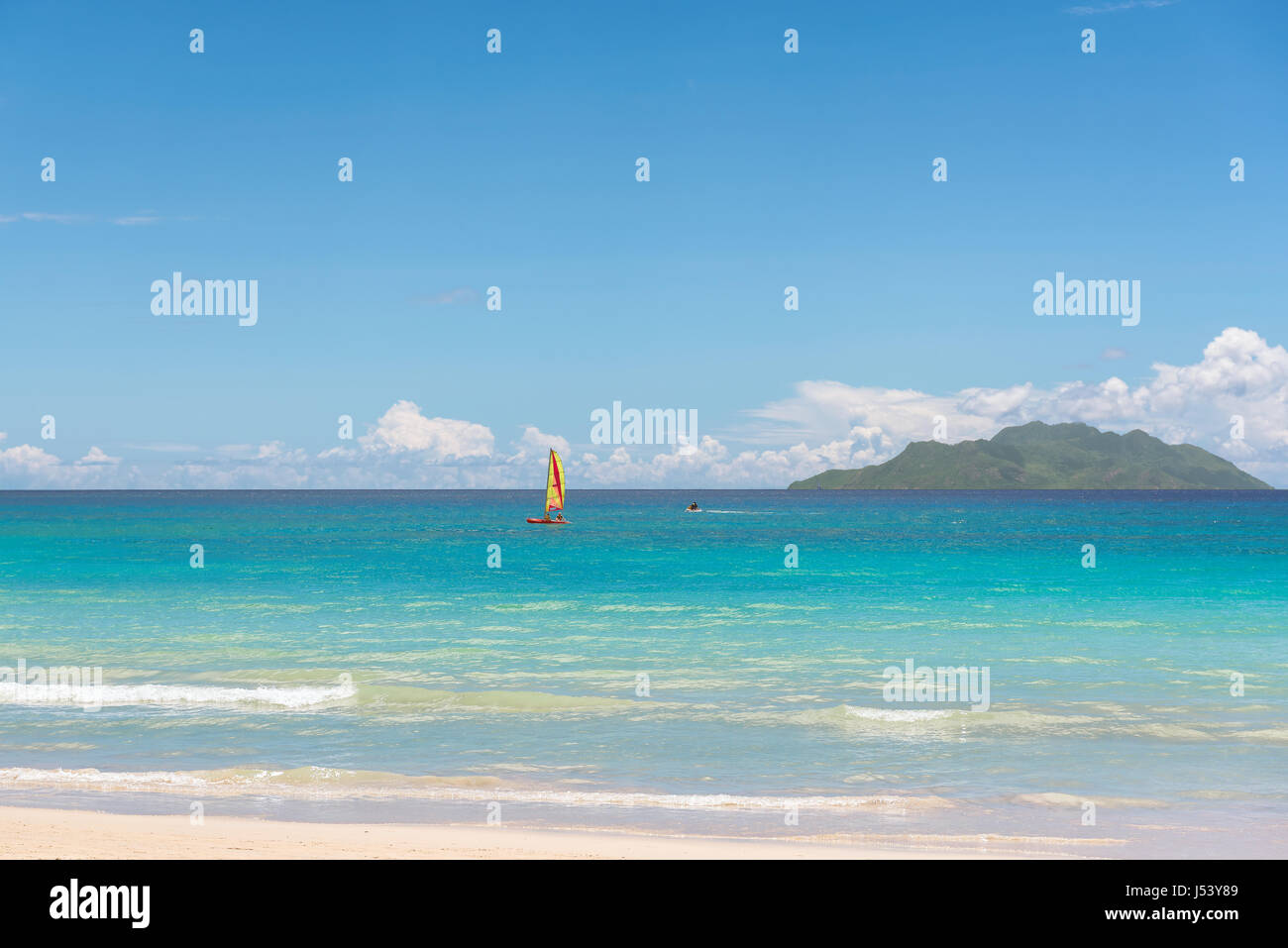 Tropical beach, sailing boat and island in the ocean. - Stock Image