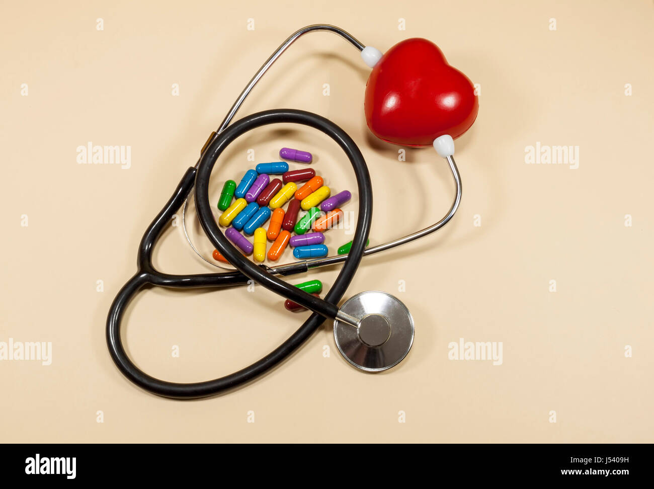 Red spongy heart locked between the arms of a medical stethoscope and colored pills , concept about cardiovascular - Stock Image