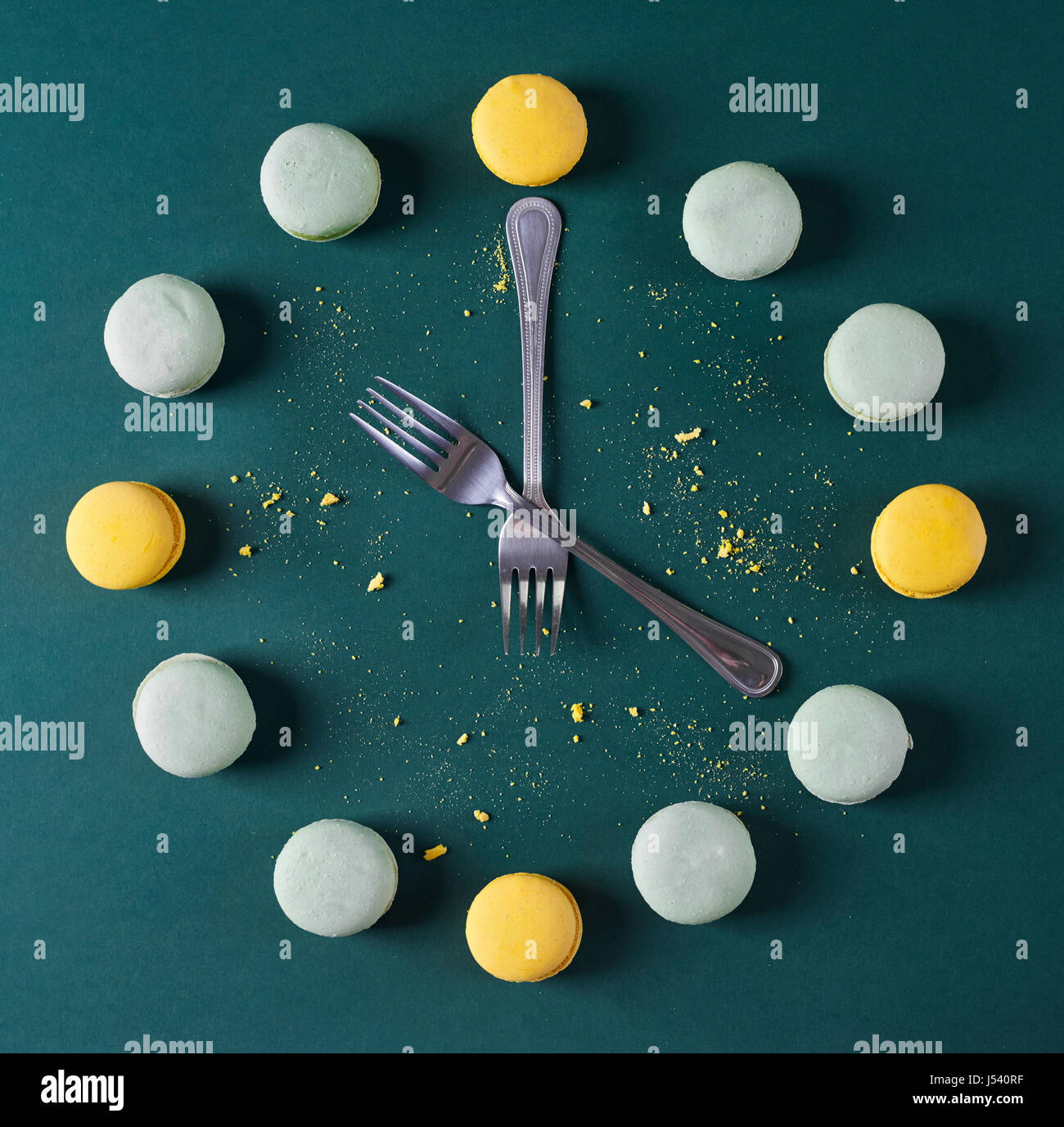 Modern clock done with forks and macaroons - Stock Image
