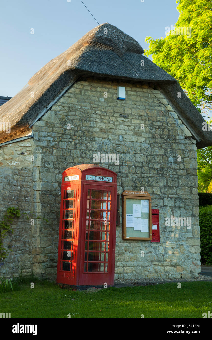 Iconic red telephone box in Buckland, a small Cotswold village in Gloucestershire. - Stock Image