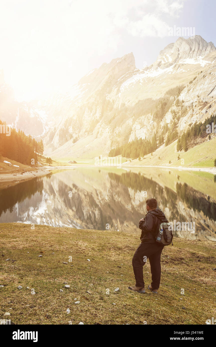 back of hiker with backpack who watching to the lake and mountains of Seealpsee, Switzerland - Stock Image