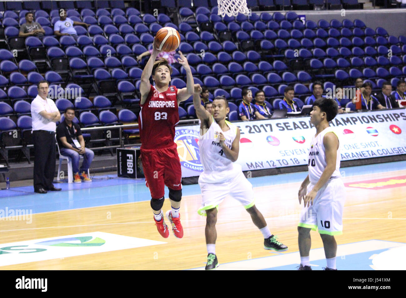 Tan Chin Hong (83) of Singapore takes a jumpshot over guard Myat Aung (4) of myanmar during their basketball game. - Stock Image