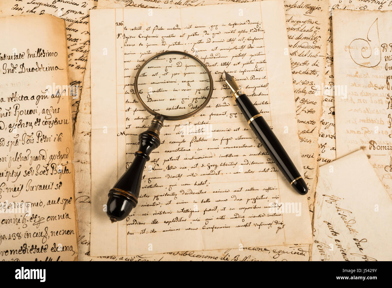 Fountain pen and magnifying glass on letter - Stock Image