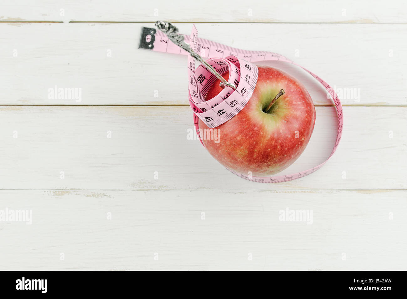 red apple with measuring tape and fork on wooden background, diet concept - Stock Image