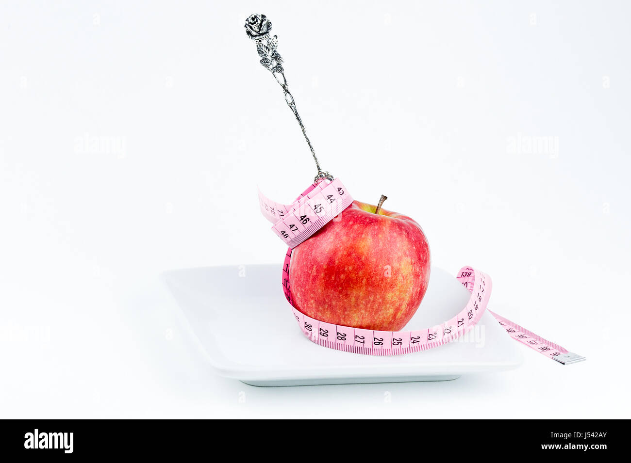 silver fork in apple on a plate with measuring tape, diet concept - Stock Image