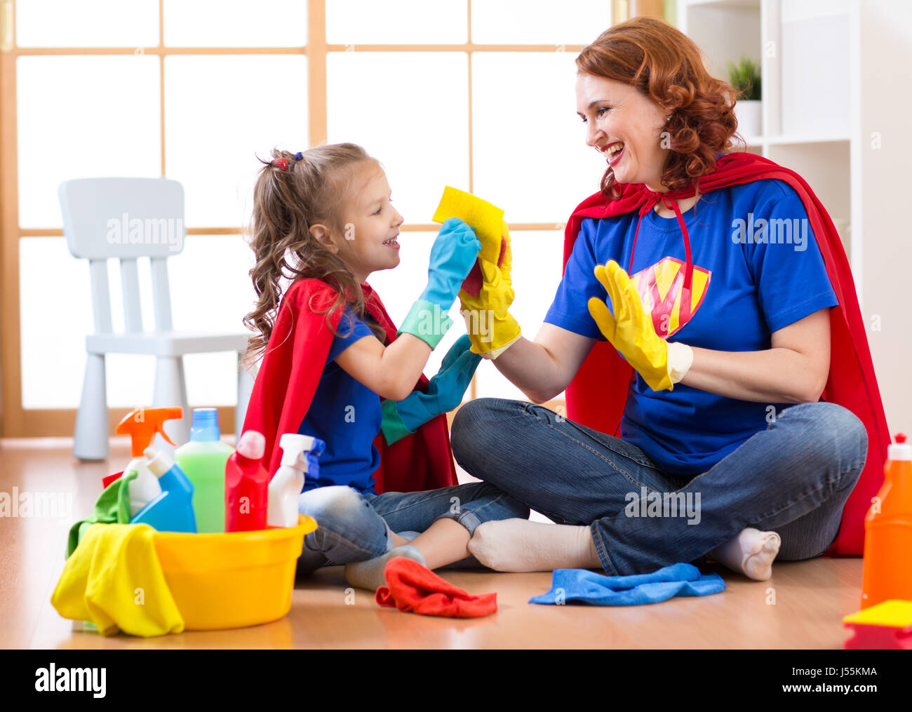 Happy woman with child cleaning room and having fun playing at home. Family housework conception. - Stock Image