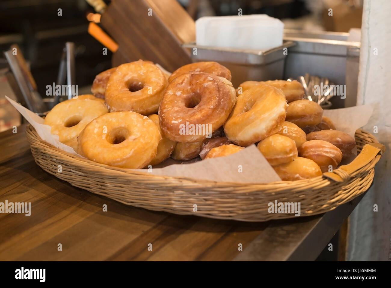 Basket of fresh glazed doughnuts in the kitchen at Native Tongues taqueria - Stock Image