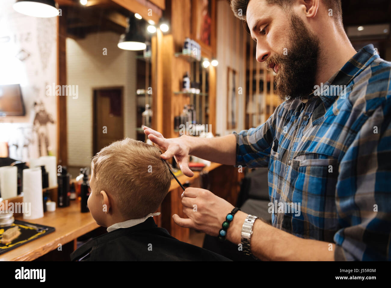 Pleasant professional barber looking at the boys head - Stock Image