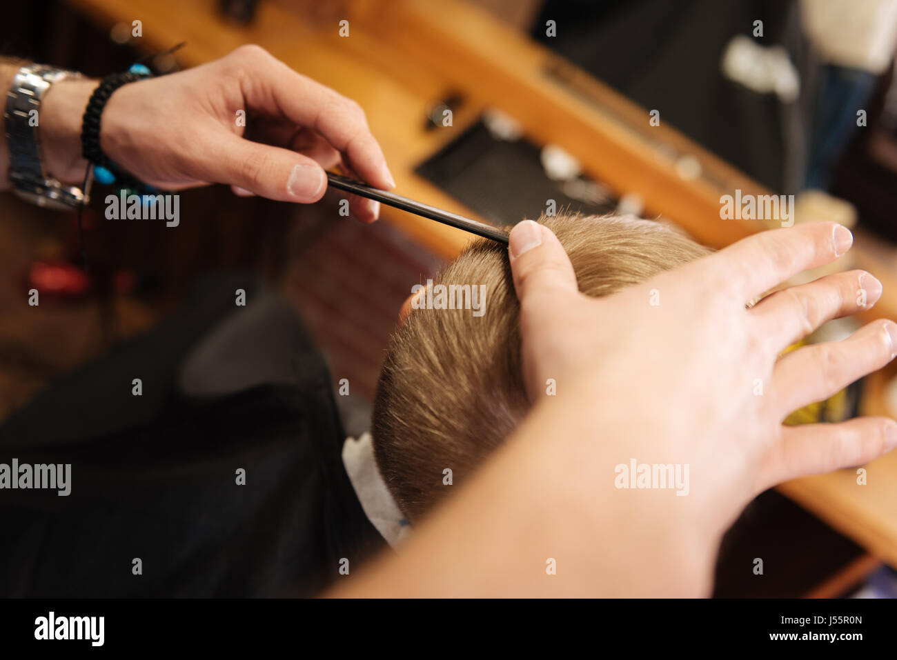 Comb being used by a professional barber - Stock Image