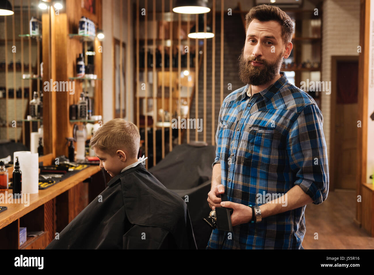 Nice good looking barber holding a comb - Stock Image