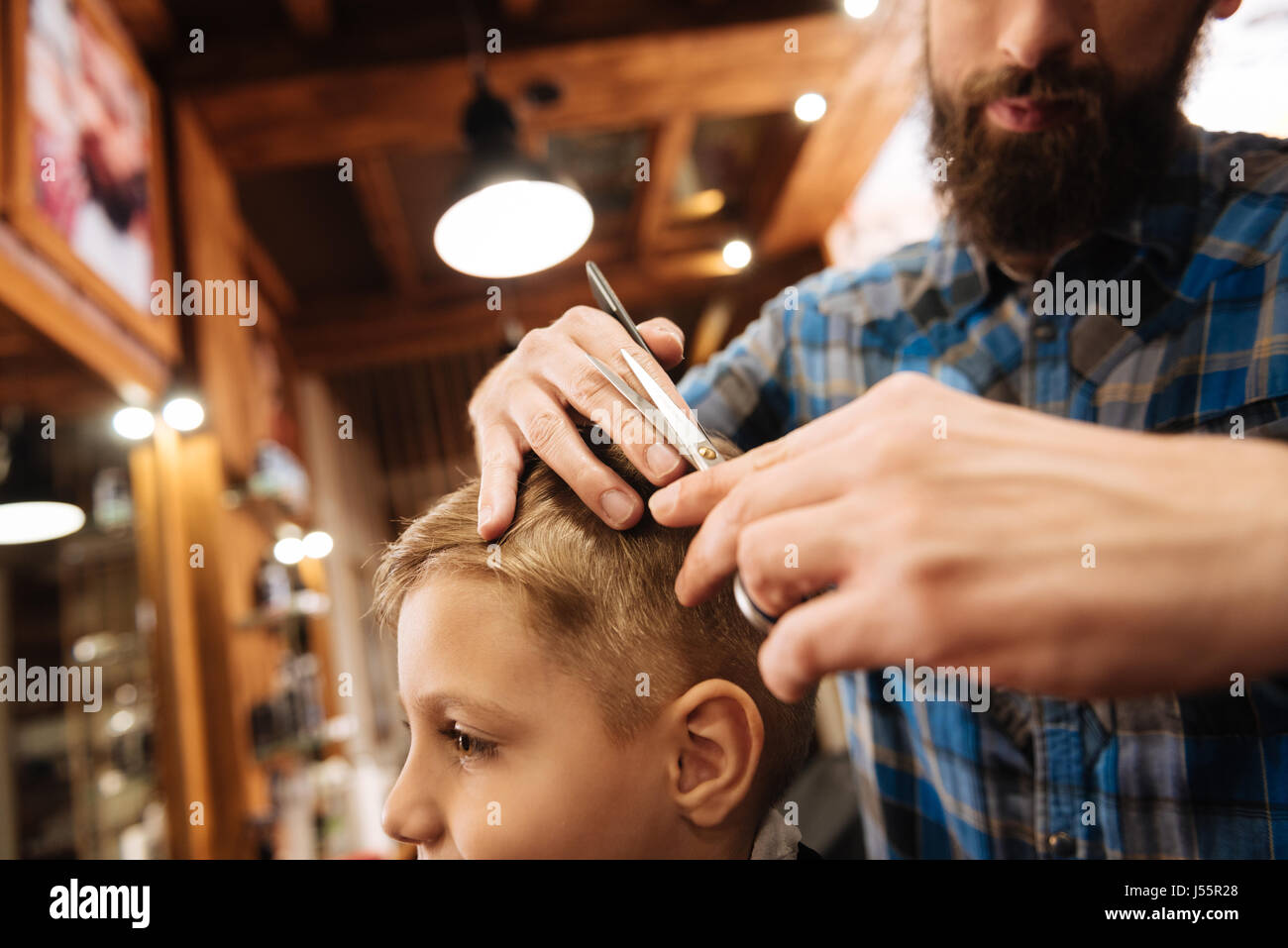Good looking young barber using scissors - Stock Image