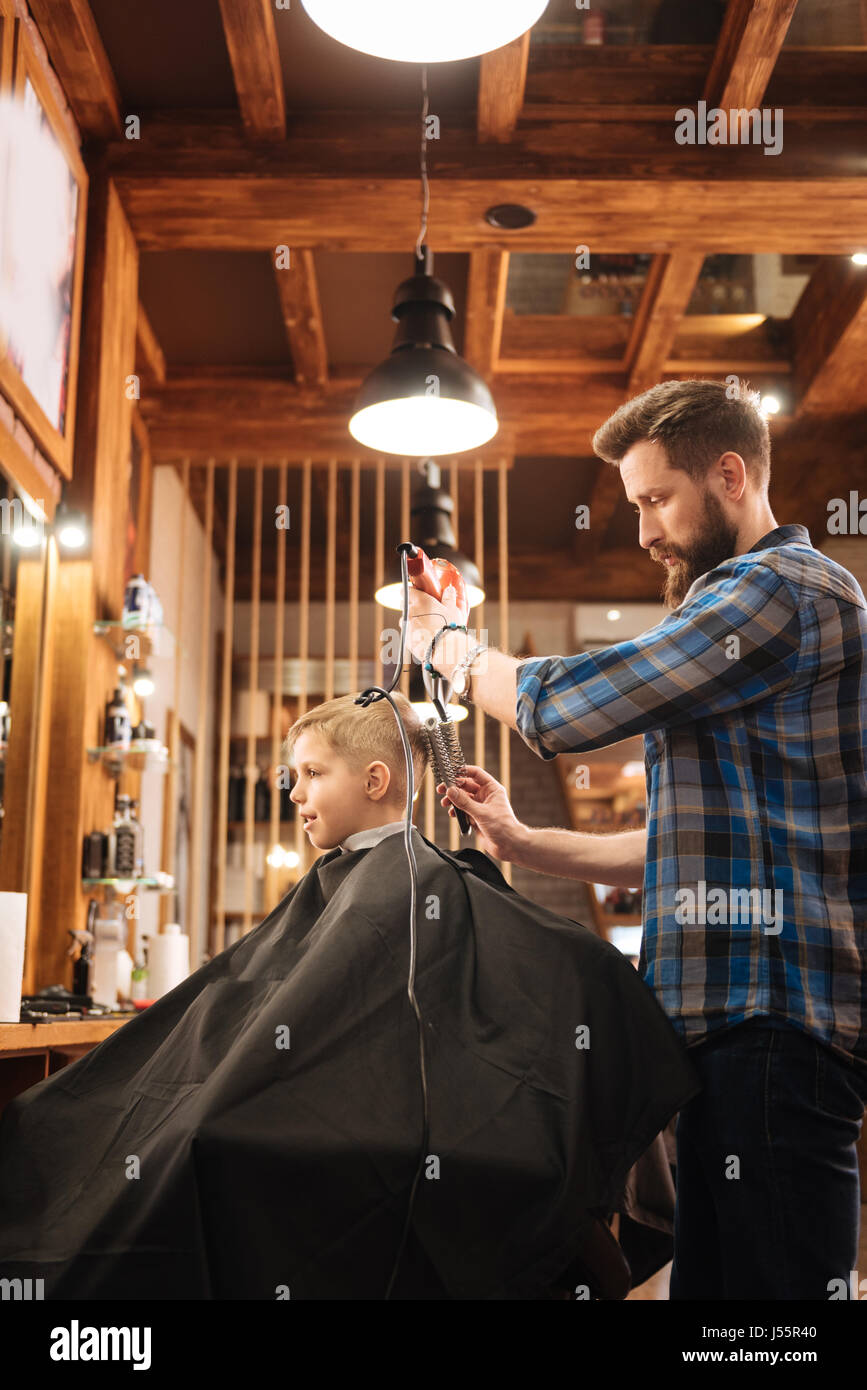 Nice experienced hairdresser working with a hair dryer - Stock Image