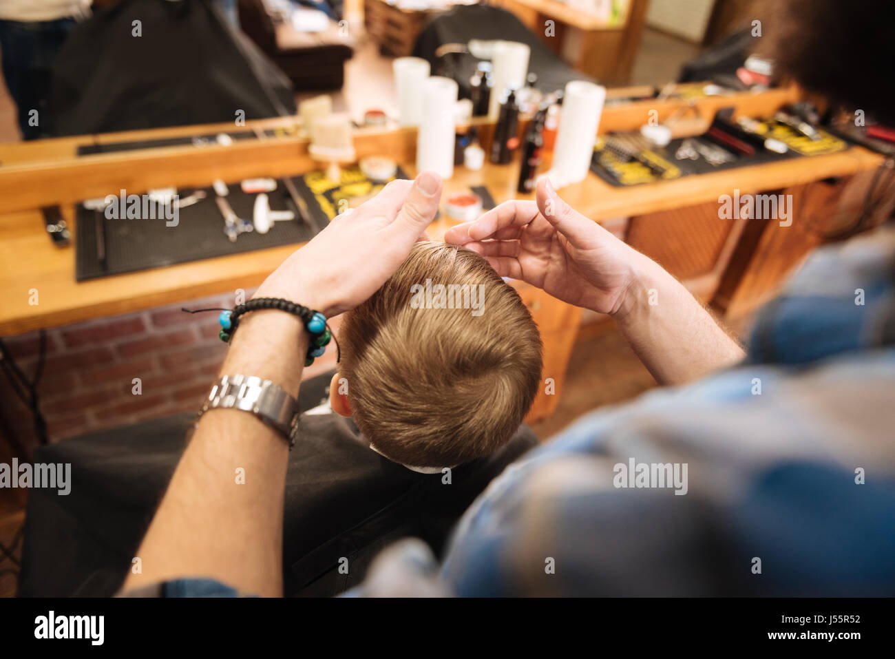 Pleasant professional hairdresser working with his client - Stock Image