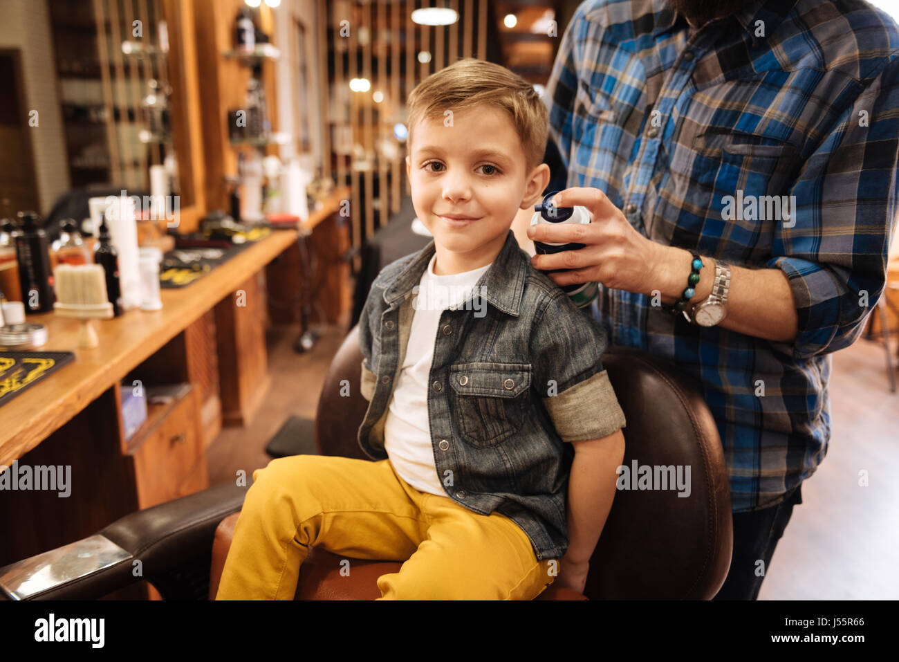 Happy nice boy being in the barbershop - Stock Image