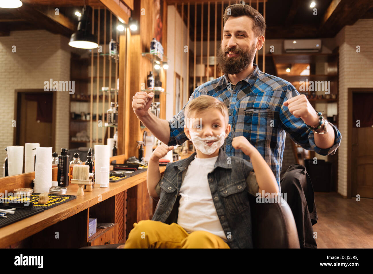 Happy nice boy showing his strength - Stock Image