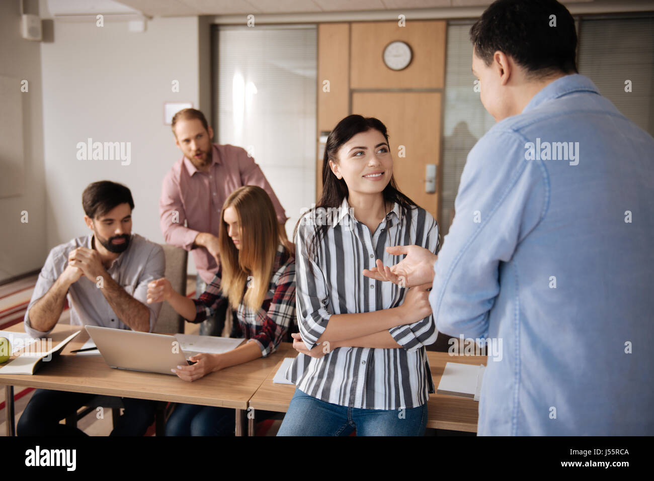 Pretty brunette looking at her colleague - Stock Image