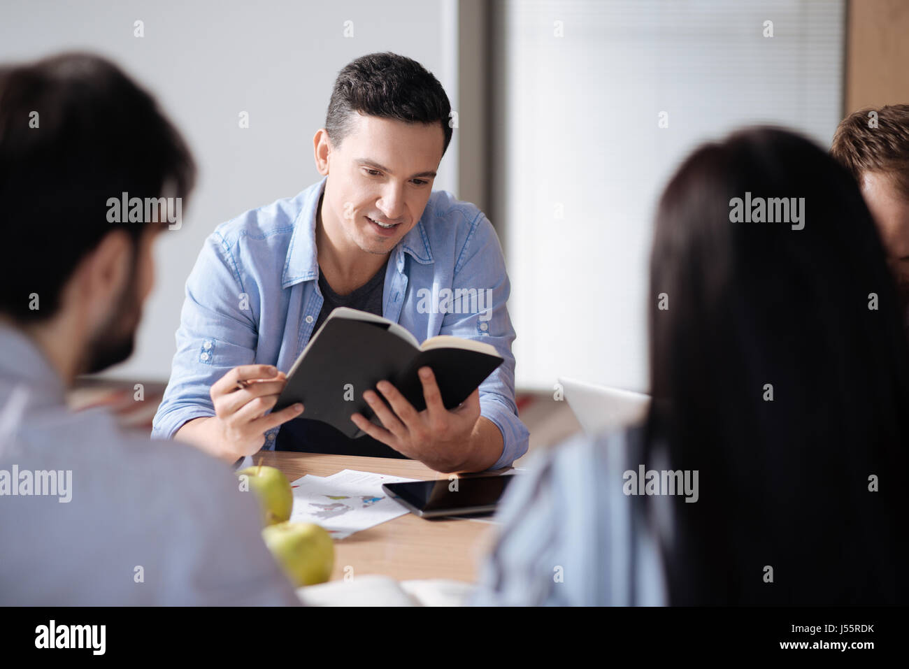 Attractive young man looking into his notebook - Stock Image