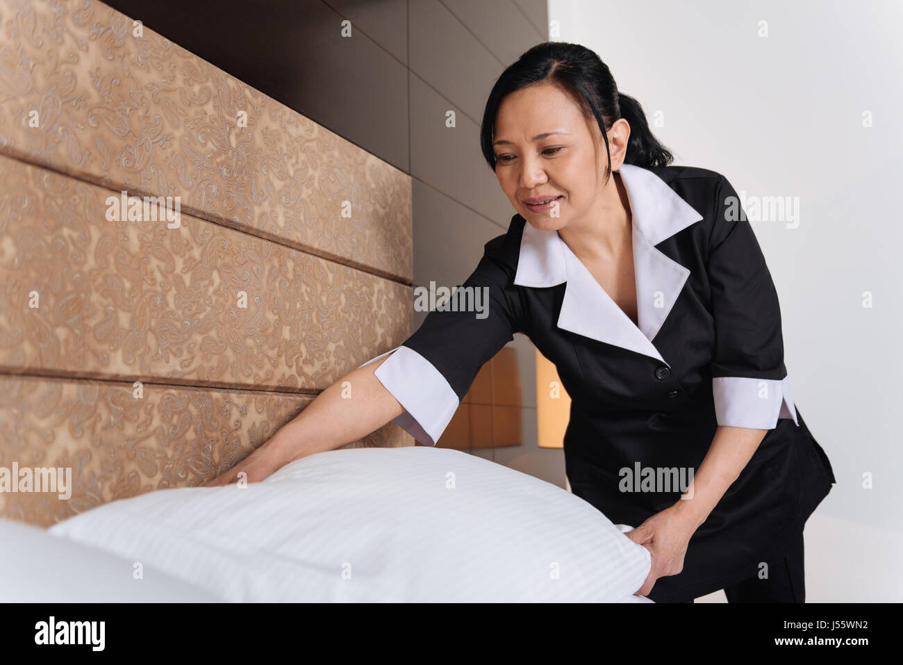 Nice pleasant woman working in the hotel room - Stock Image