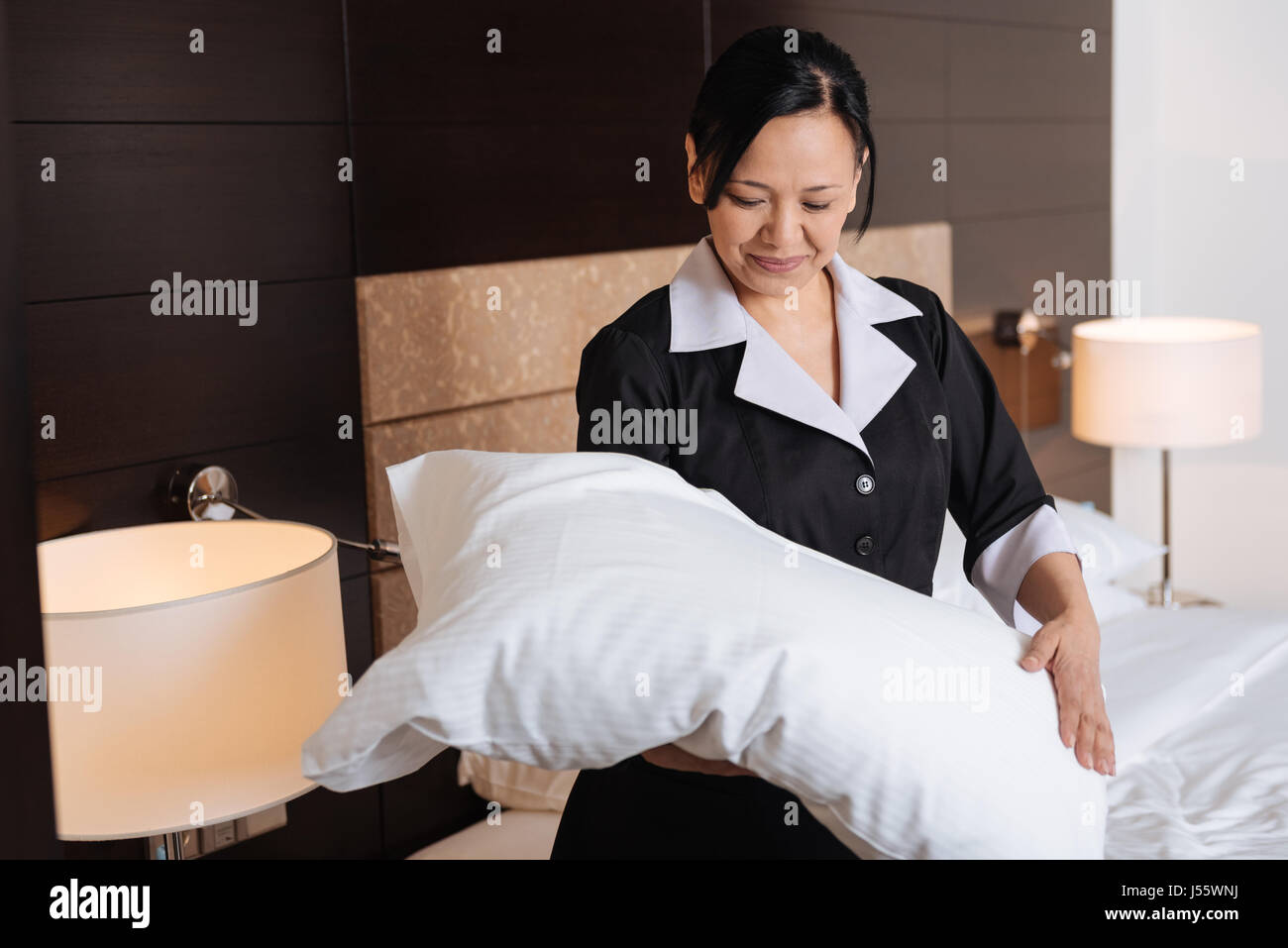 Positive hard working hotel maid looking at the pillow - Stock Image