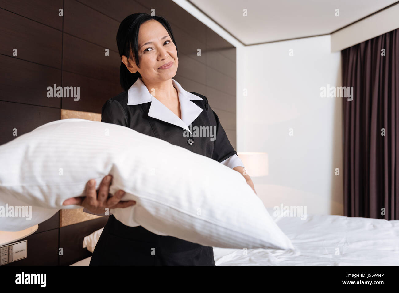 Joyful Asian hotel maid standing in the hotel room - Stock Image