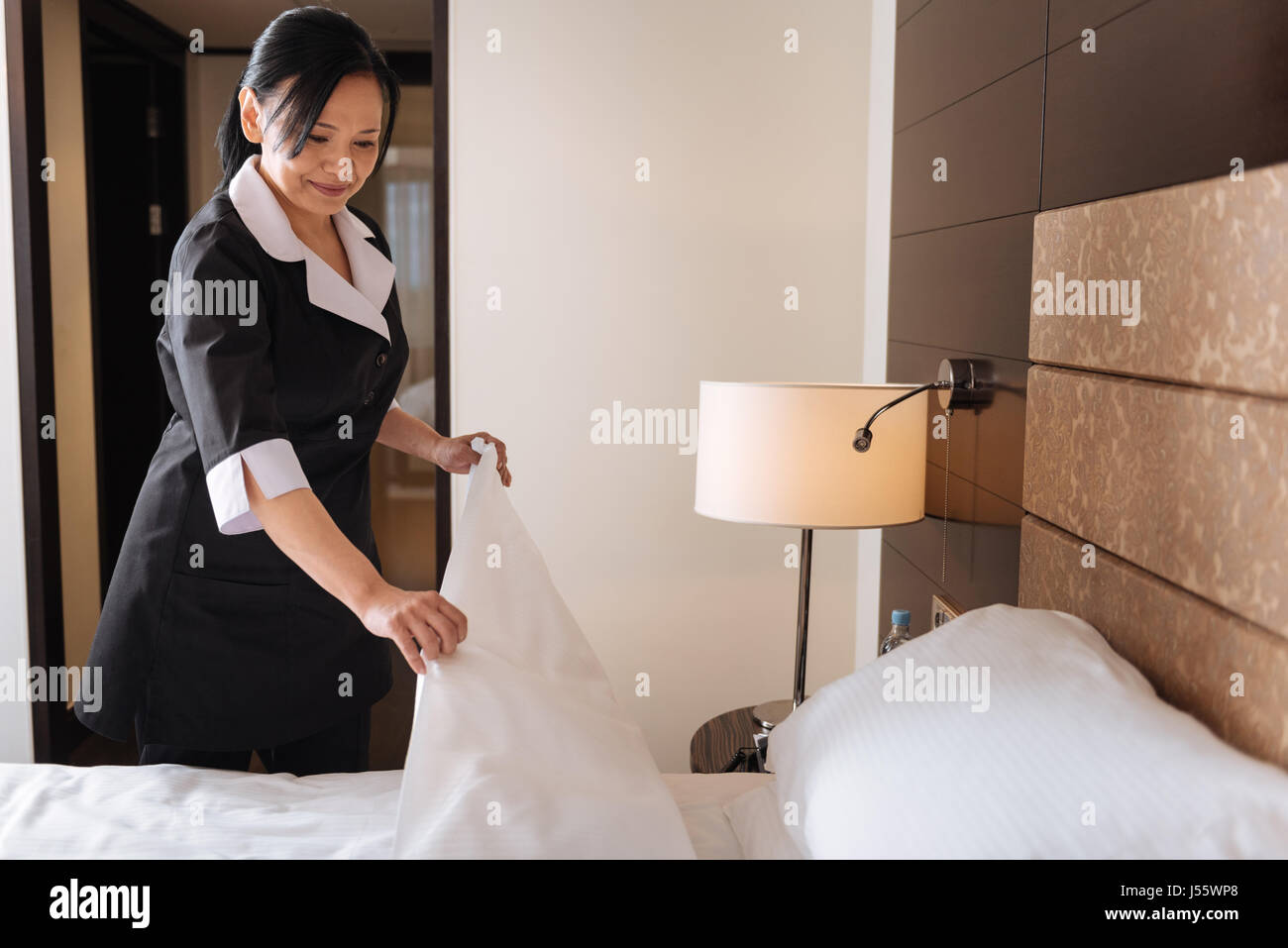 Positive nice hotel maid looking at the bed - Stock Image