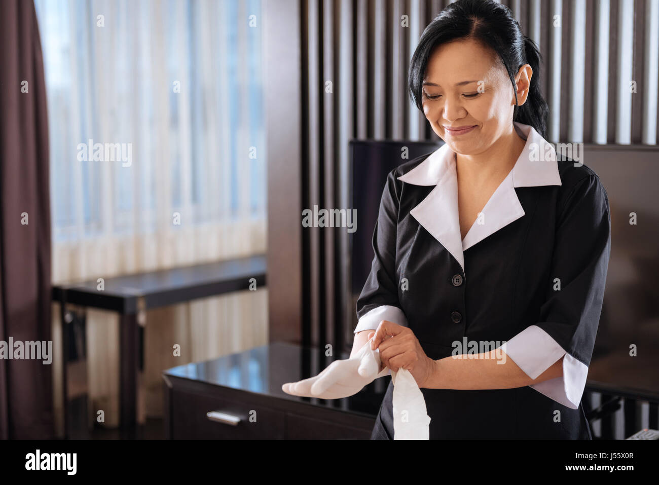 Nice pleasant hotel maid wearing disposable gloves - Stock Image