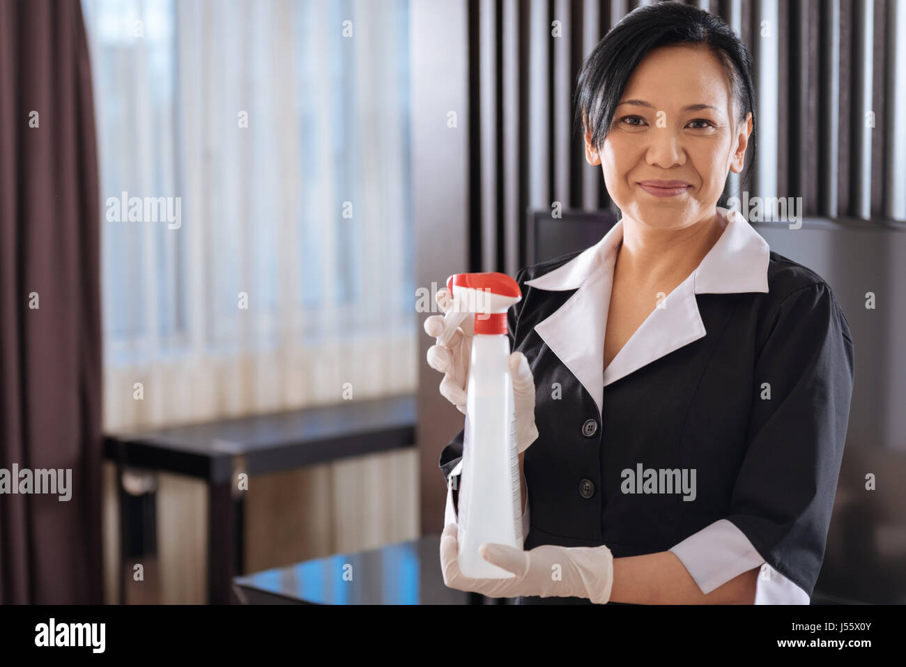 Positive Asian hotel maid holding a cleansing agent - Stock Image