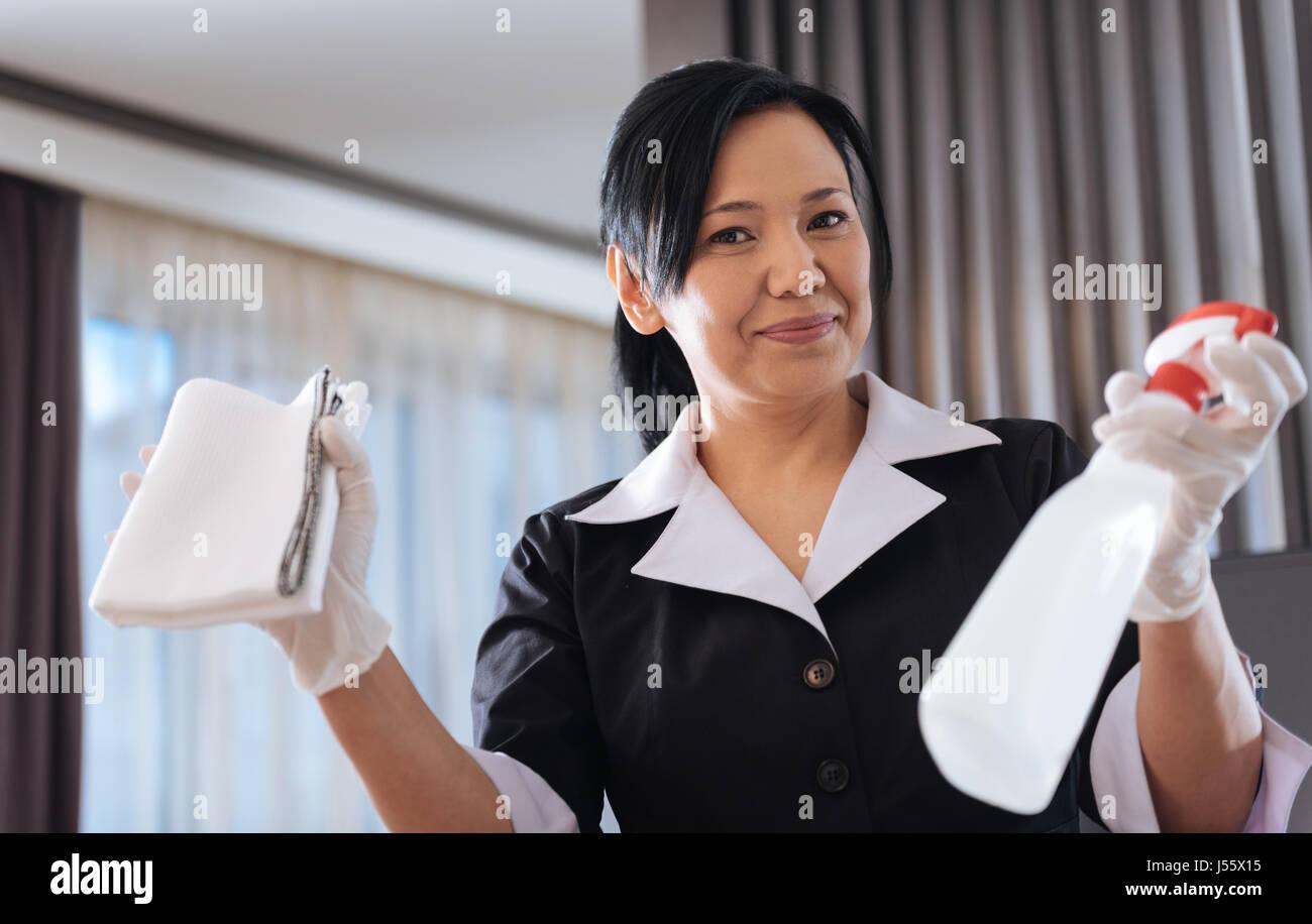 Joyful nice hotel maid showing her equipment - Stock Image