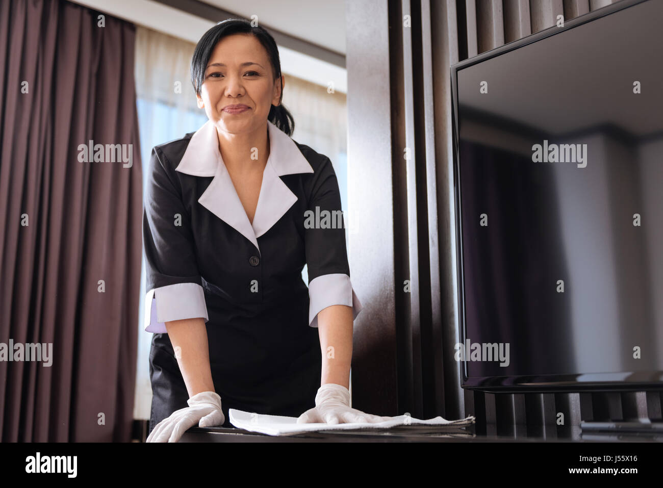 Hard working Asian hotel maid wiping the dust - Stock Image