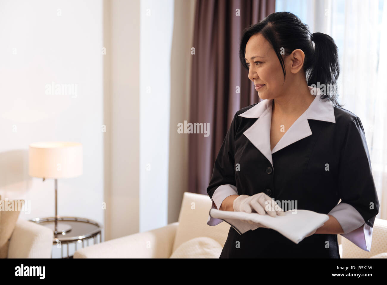 Happy delighted hotel maid standing in the room - Stock Image