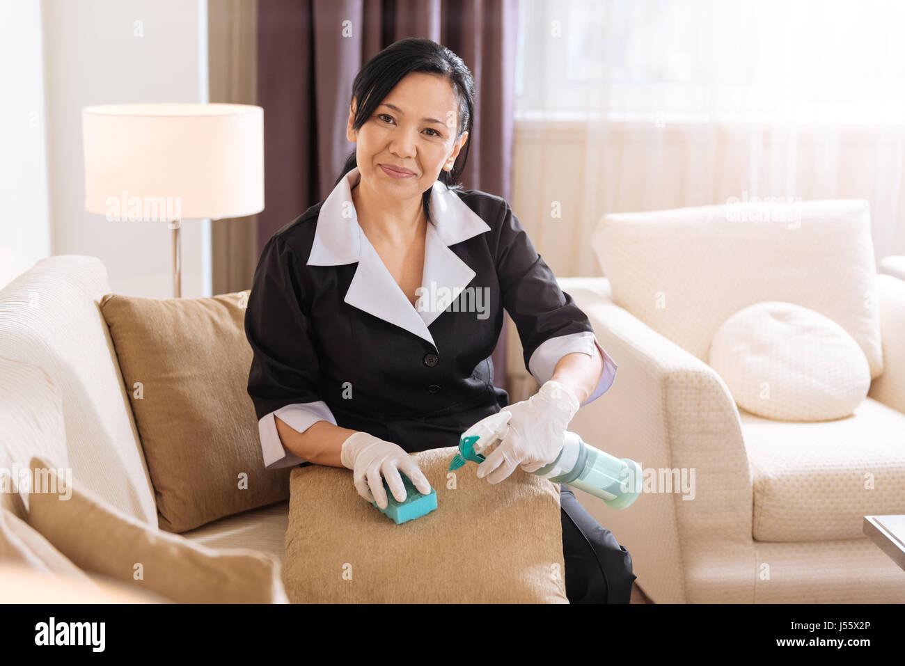 Joyful good looking chambermaid cleaning the spot - Stock Image