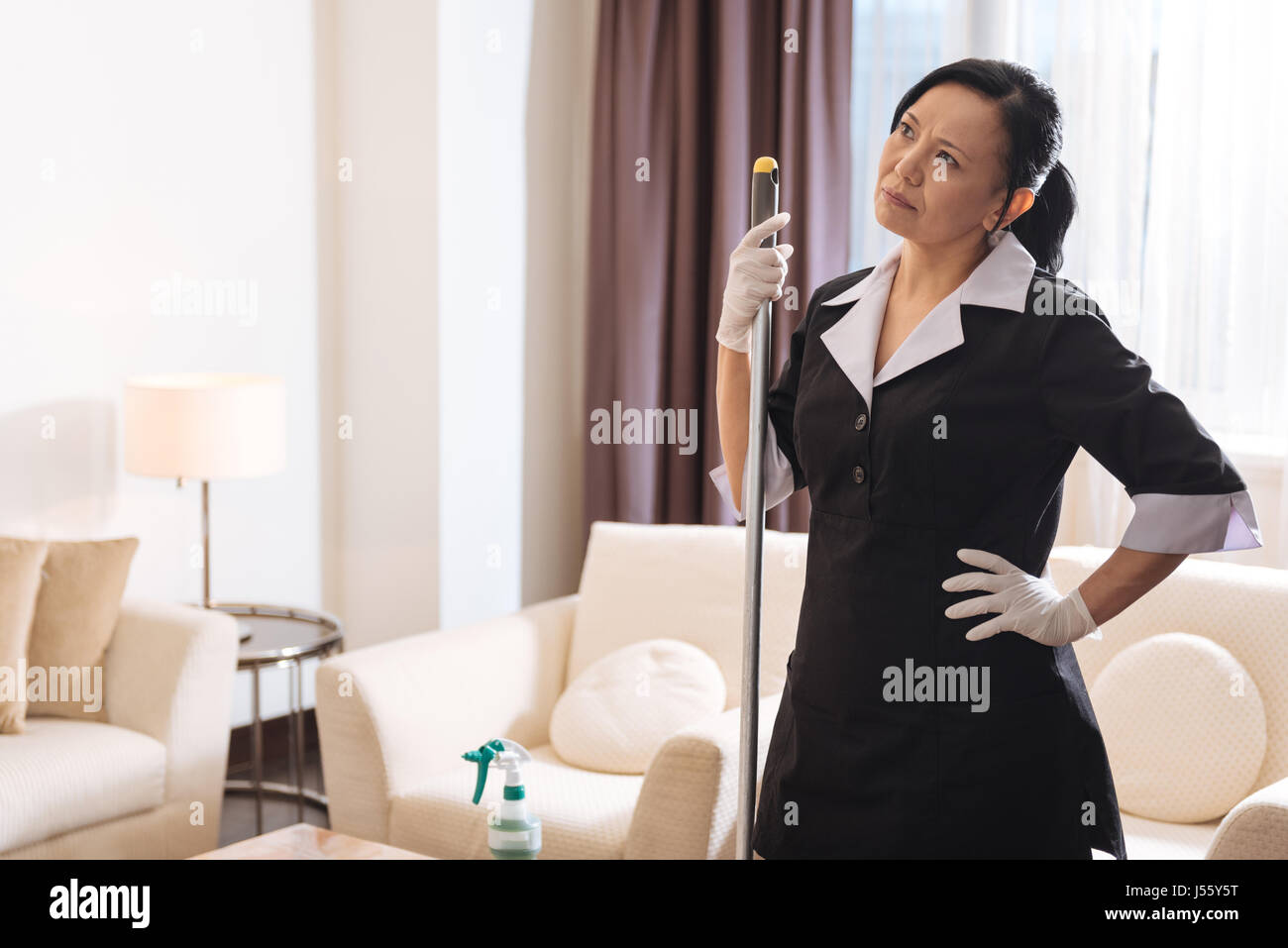 Nice thoughtful woman holding a mop - Stock Image