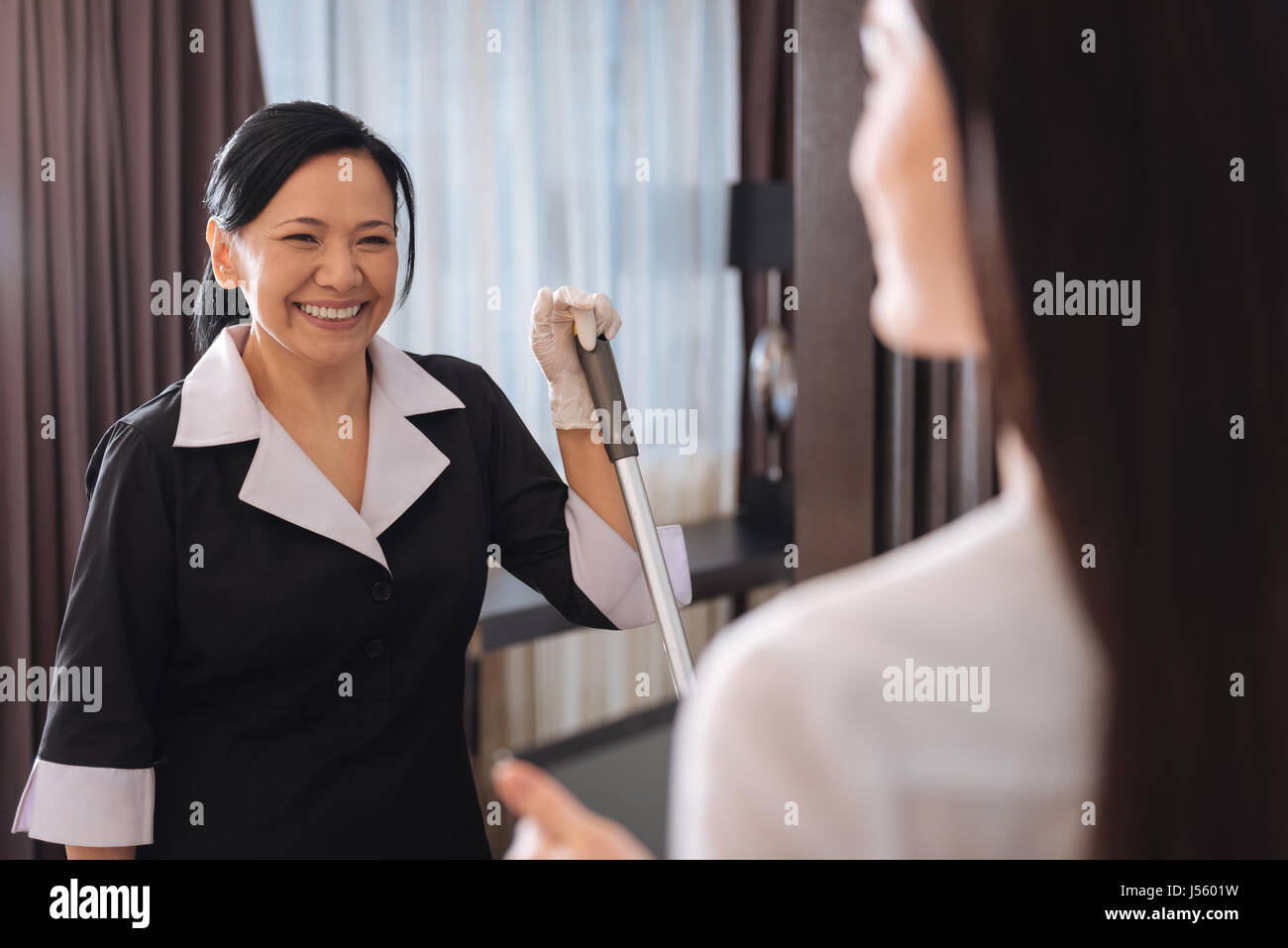Happy positive chambermaid looking at her manager - Stock Image