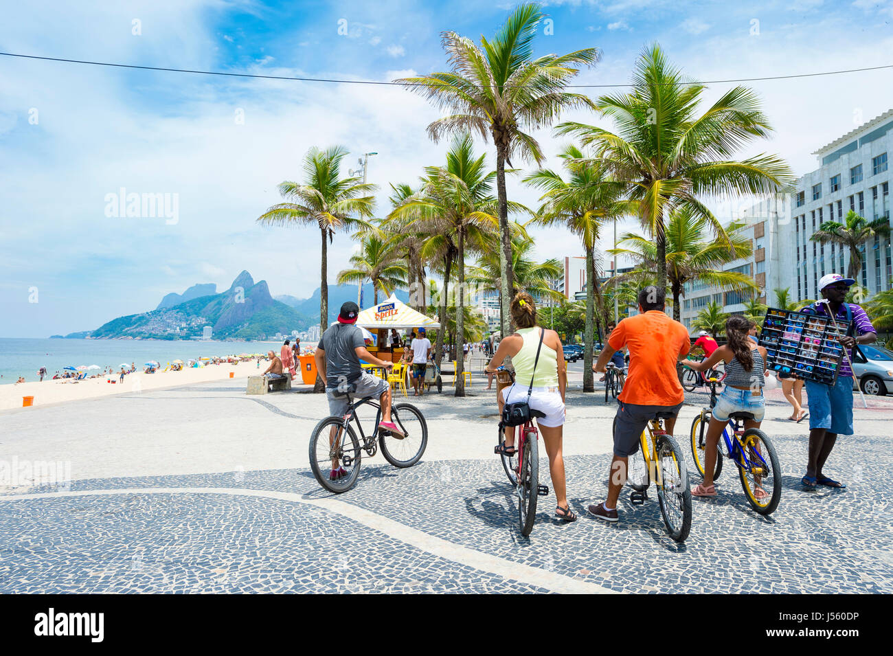 RIO DE JANEIRO - FEBRUARY 1, 2017: A group of visitors to Ipanema Beach stop their bikes on the boardwalk at Arpoador. - Stock Image