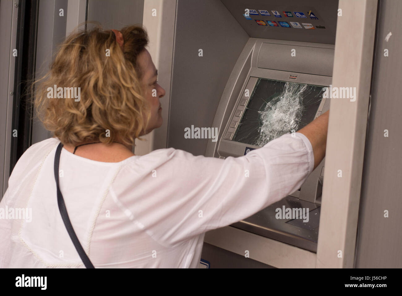 Athens, Greece. 17th May, 2017. A woman uses an atm machine that was smashed by protesters. Thousands took to the - Stock Image