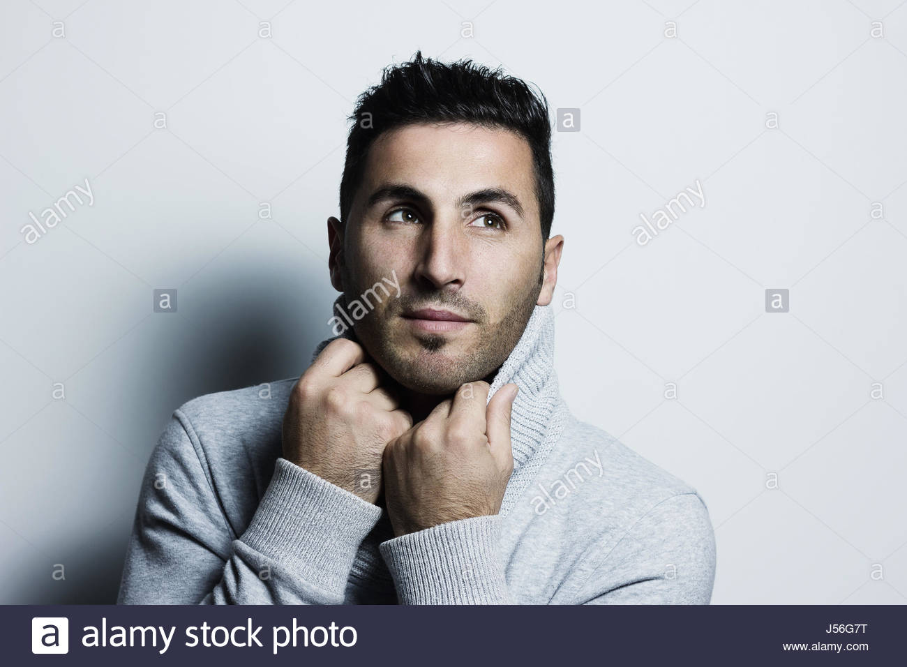 atractive young man warm up with pullover and looking sideways in front of grey background - Stock Image