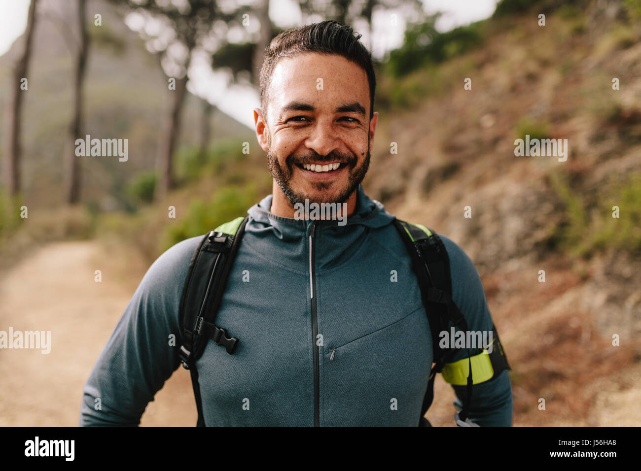 Portrait of healthy young caucasian man standing outdoors and smiling. Confident young male runner on country road. Stock Photo