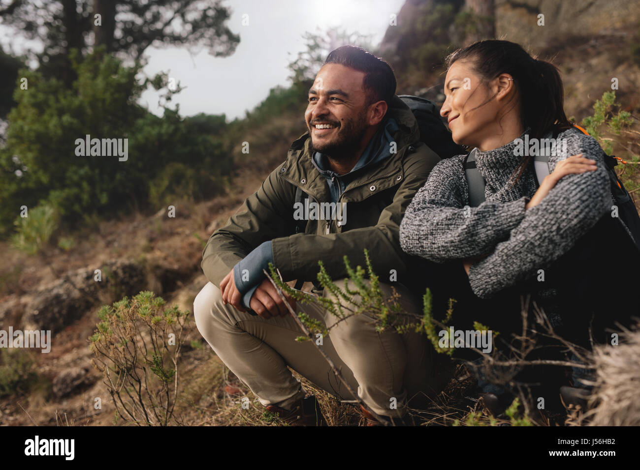Young couple out on hike in mountains. Relaxed young man and woman sitting on country path. - Stock Image