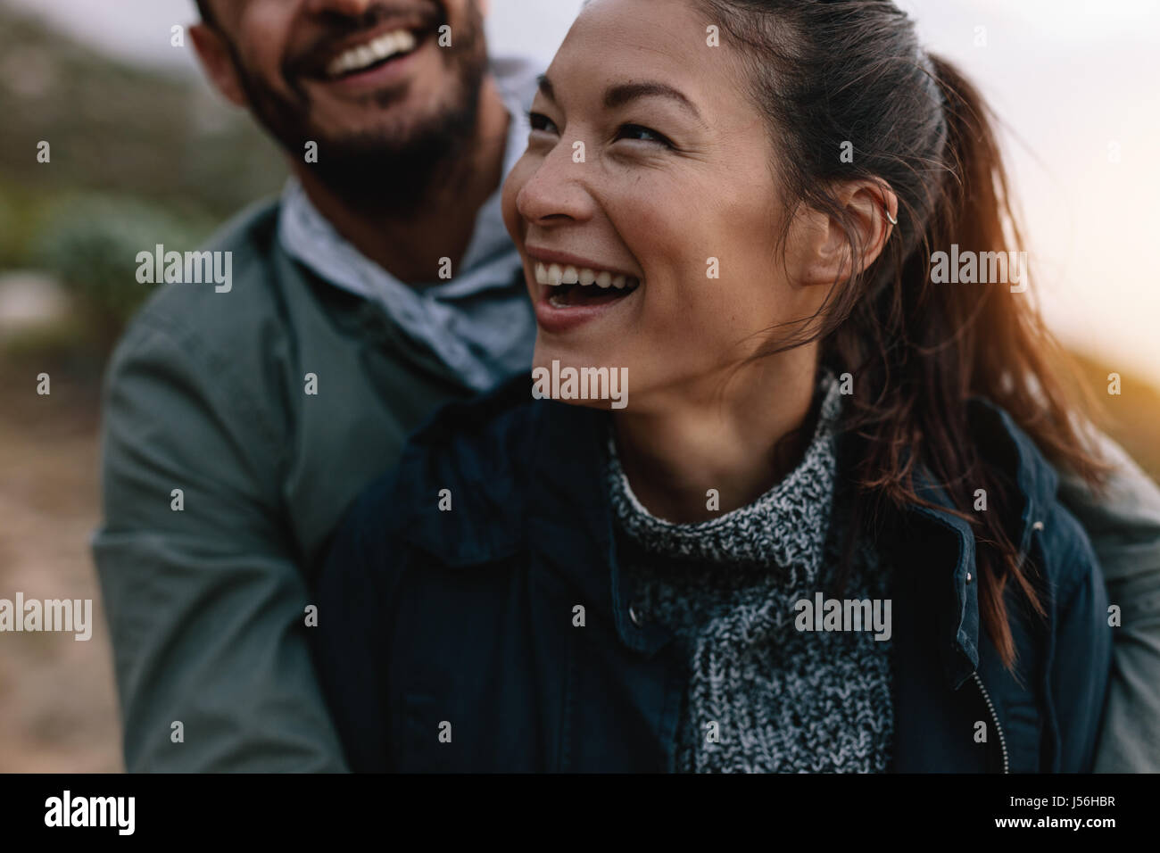 Smiling asian woman being embraced by her boyfriend from behind. Couple enjoying on vacation. - Stock Image