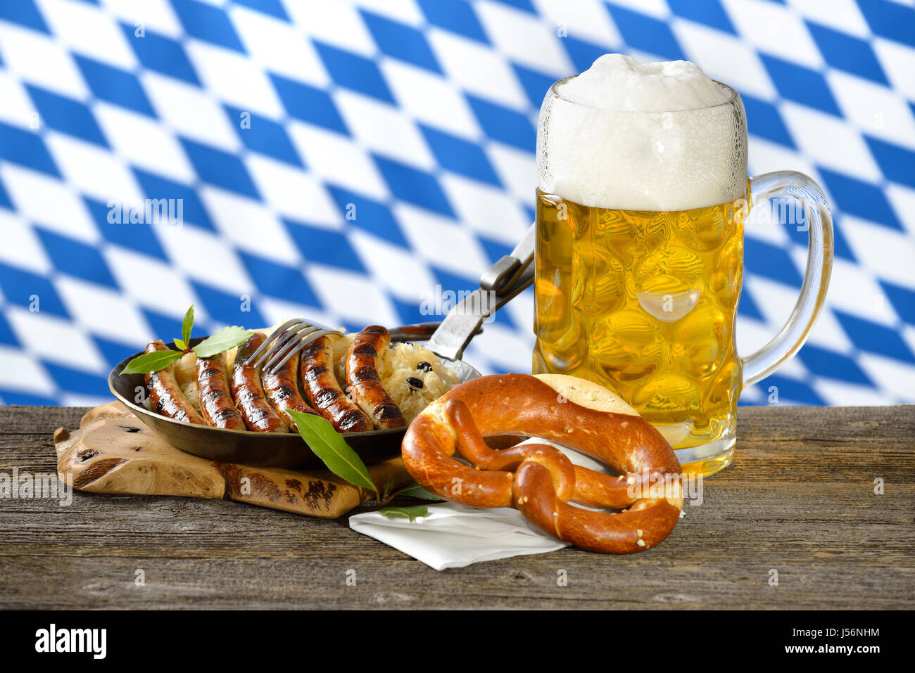 Fried Nuremberg sausages on sauerkraut with a mug of Bavarian beer and a pretzel Stock Photo