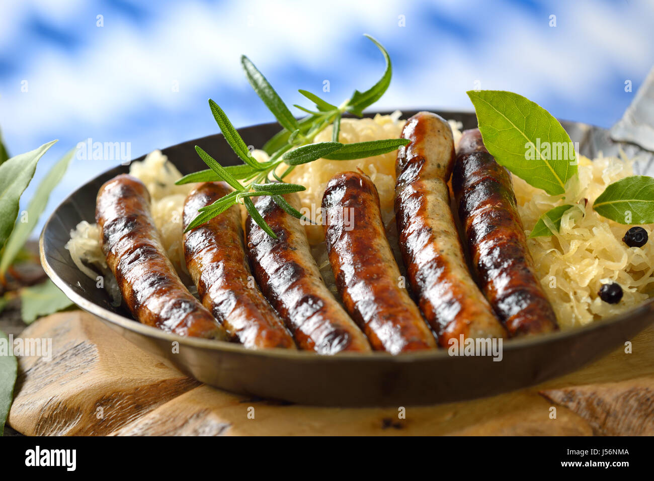 Fried Nuremberg sausages on sauerkraut served in an iron frying pan, in the background the Bavarian flag Stock Photo