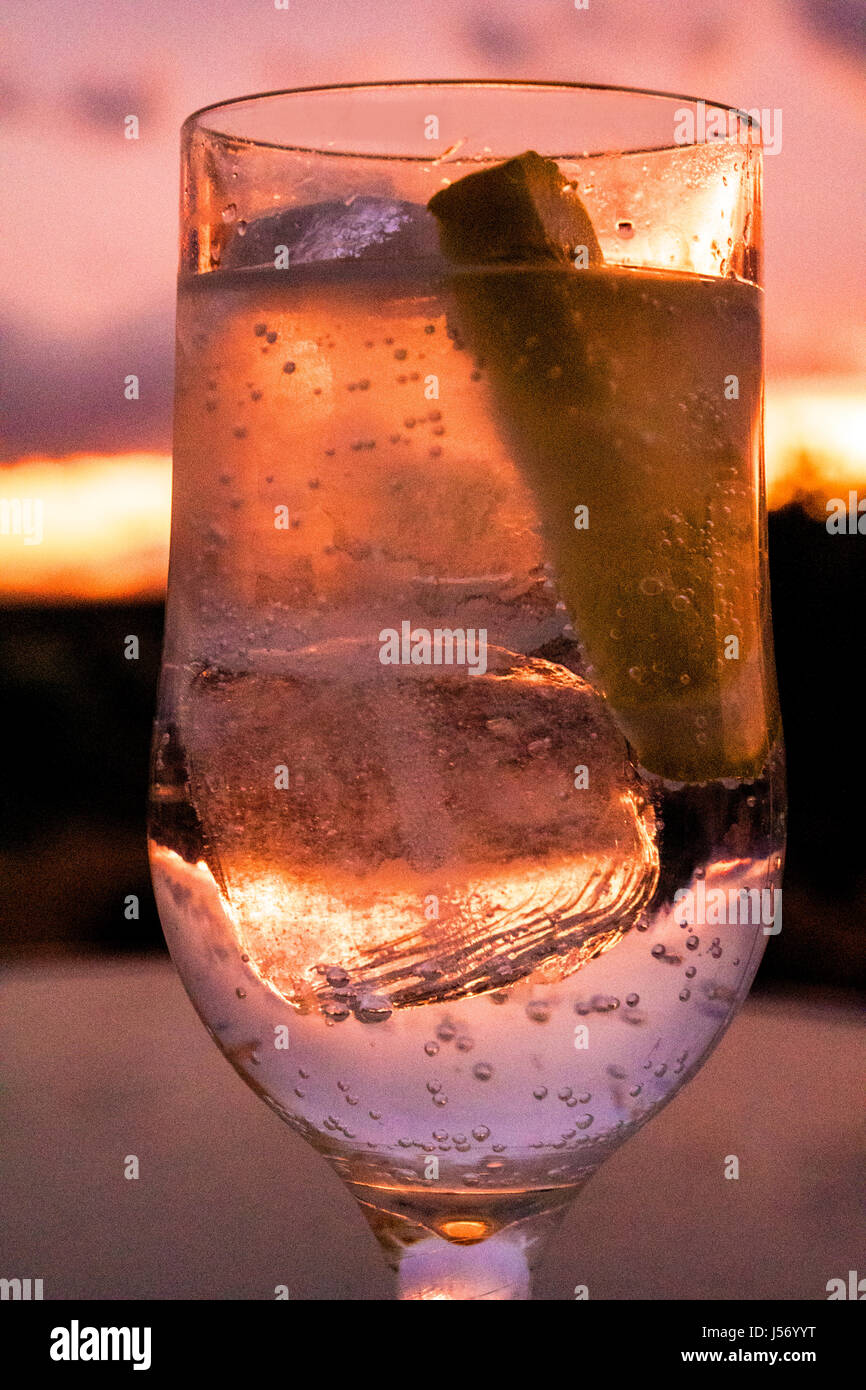 glass of drink with ice and lemon at sunset - Stock Image