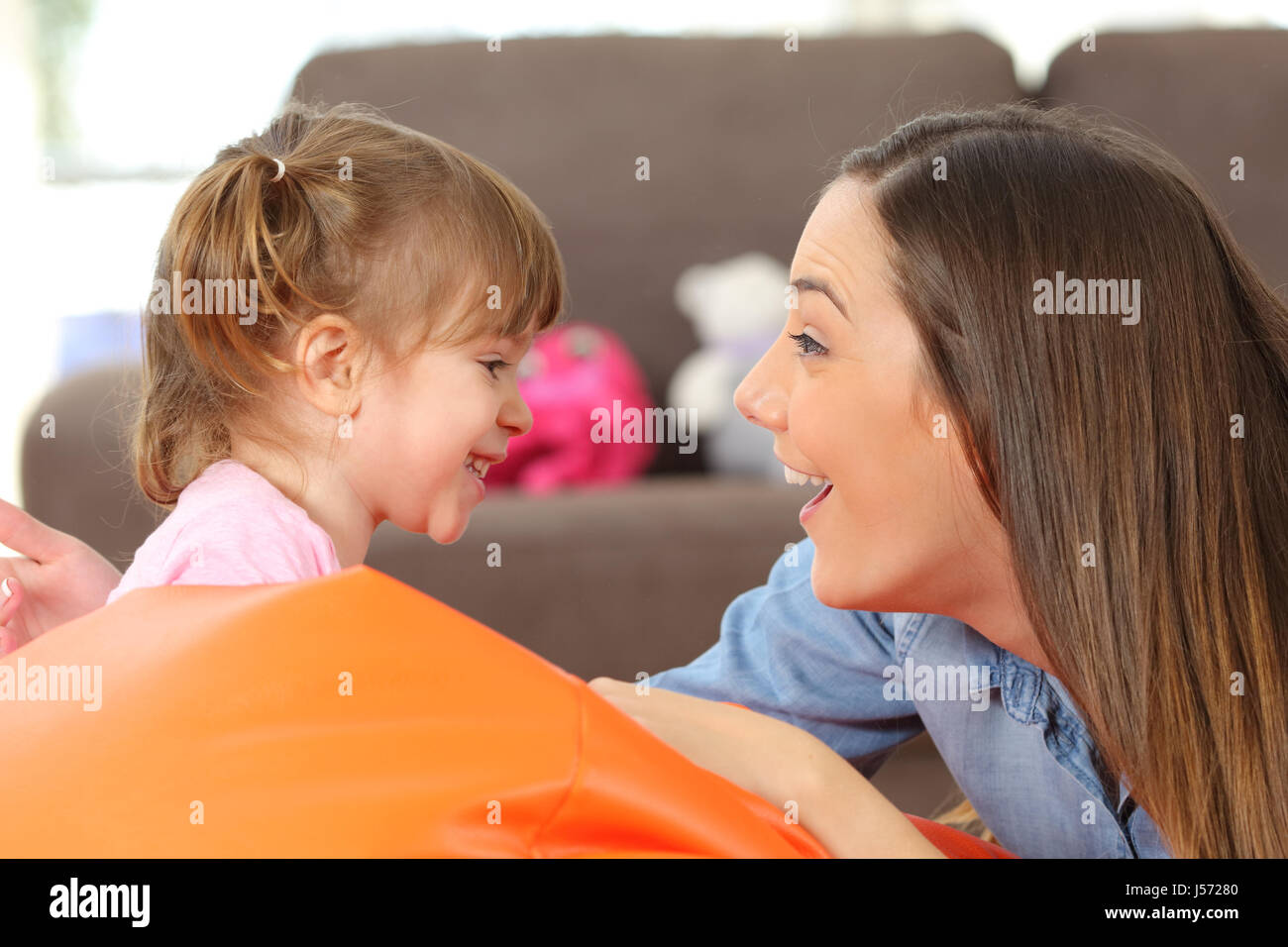 Side view portrait of a happy mother and 2 years baby daughter facing and joking in the living room at home - Stock Image