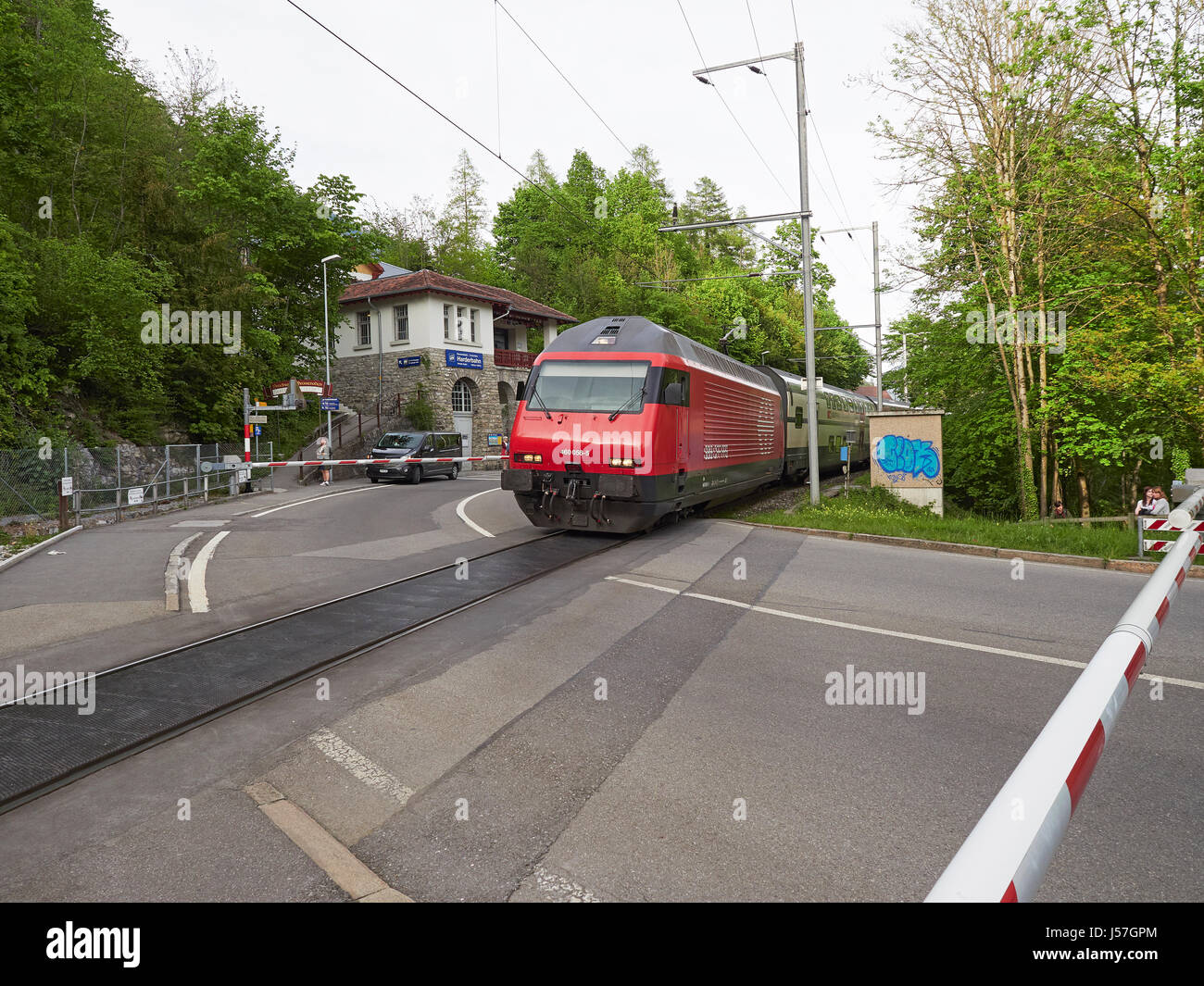 Switzerland an SBB intercity IC train leaving Interlaken Ost for Bern passing the Harder Kulm funicular station - Stock Image
