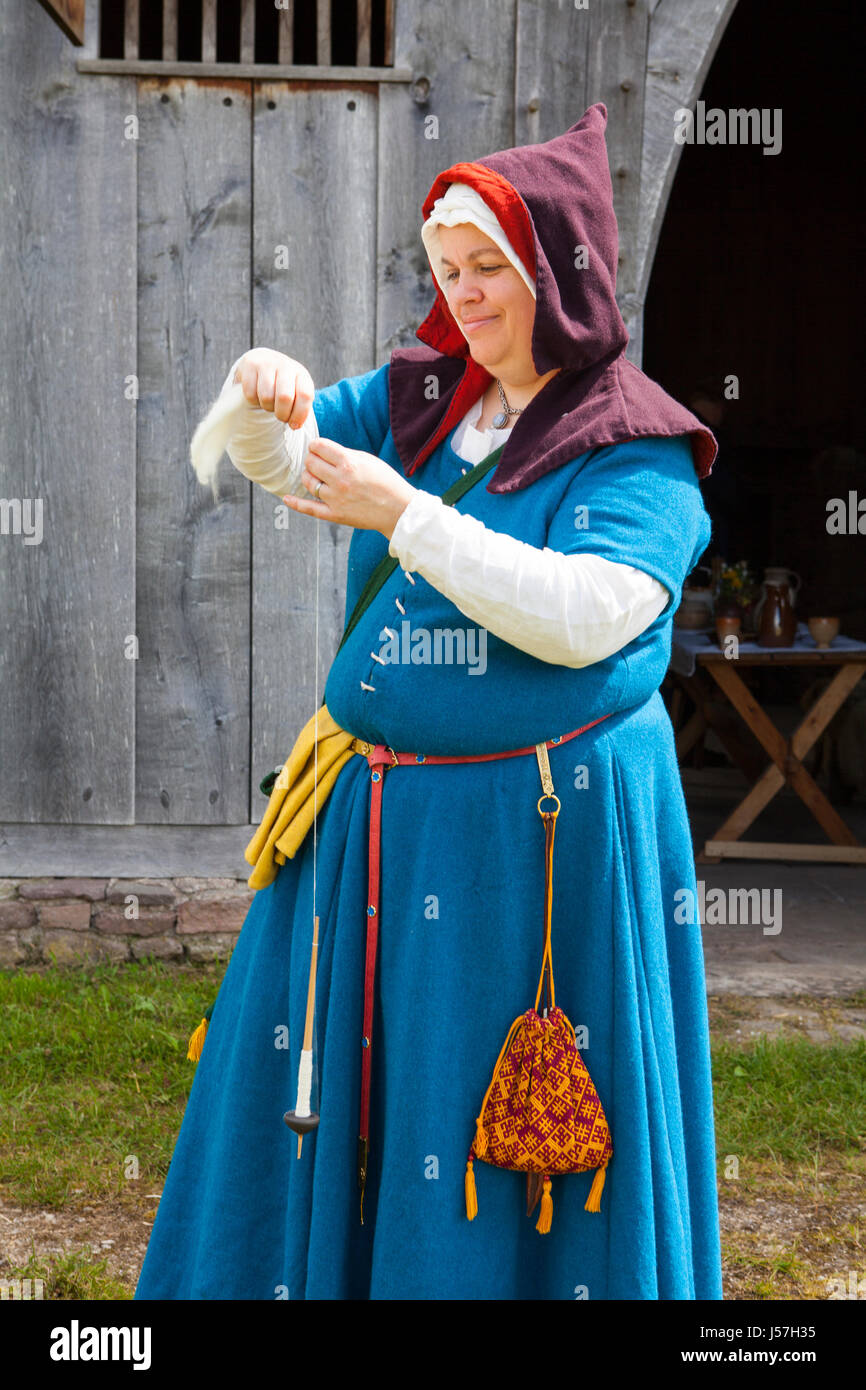 Spinning yarn by a member of a reenactment group, reconstructed medieval house, Nienover, Bodenfelde, Lower Saxony, Stock Photo