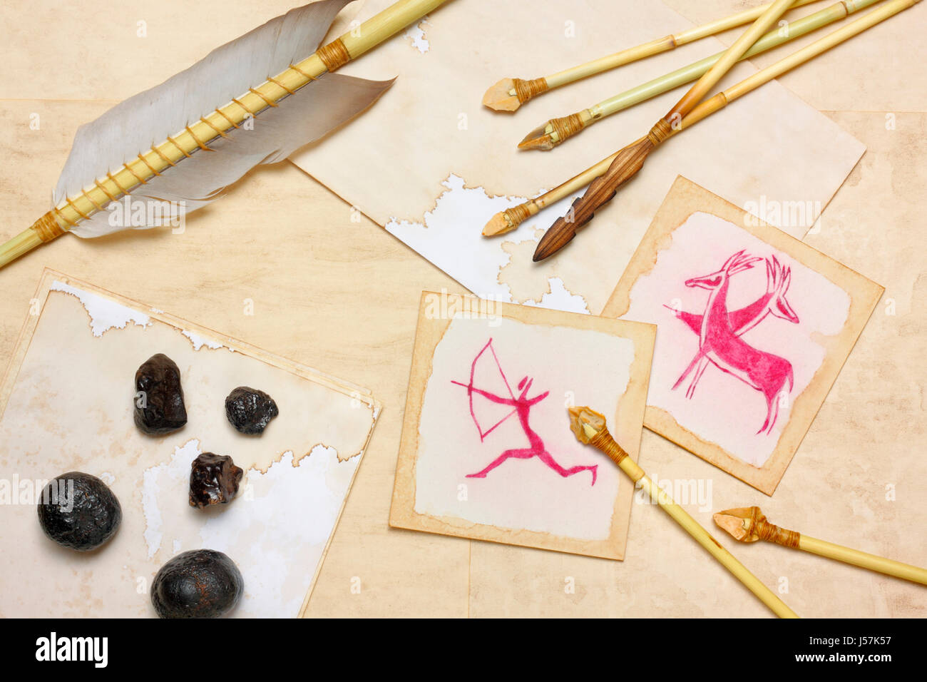 Nostalgic vintage still life with hunting drawings, primitive arrows and hematite lumps over aged paper sheets - Stock Image