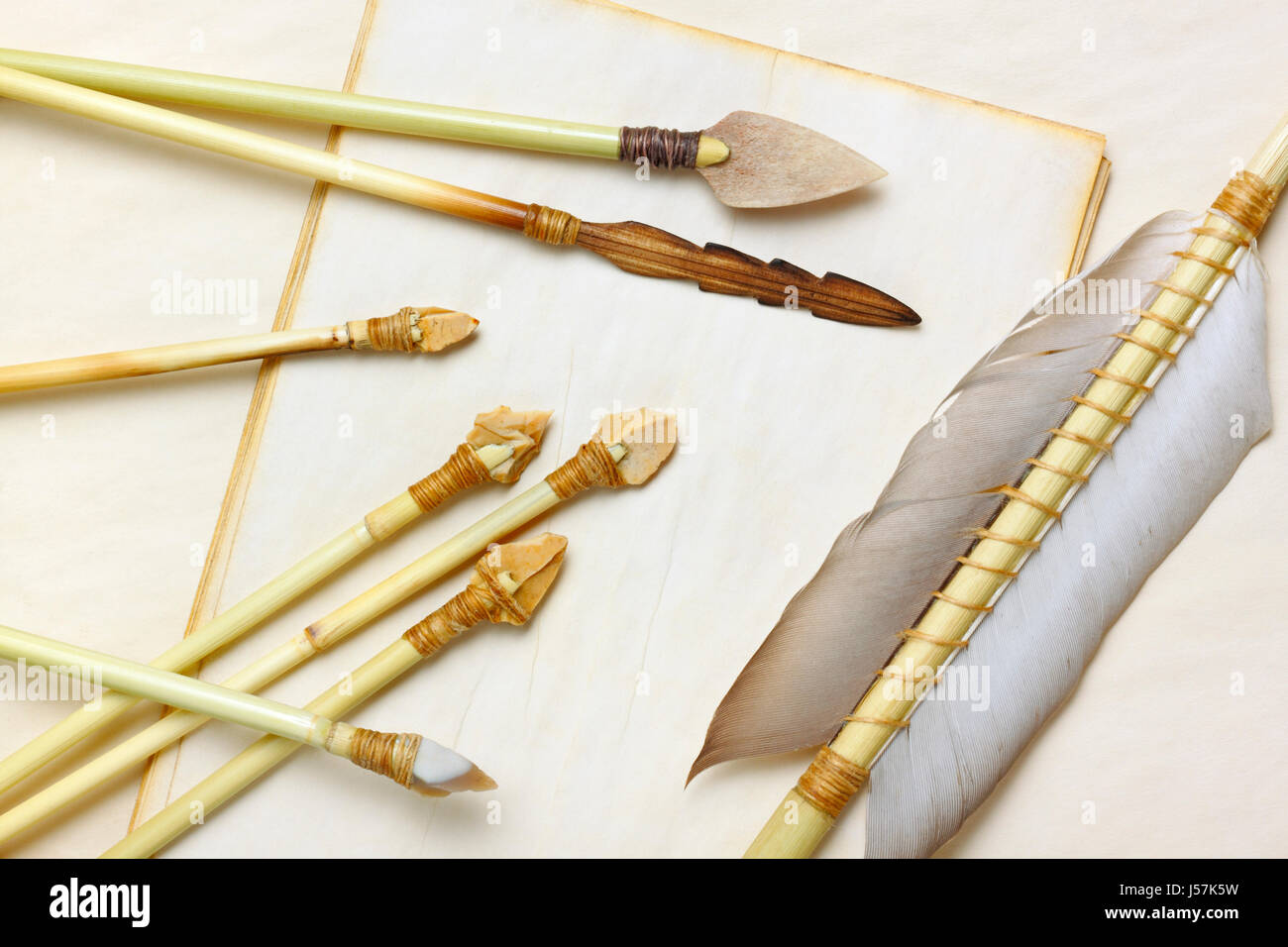 Primitive hunting and fishing arrows with flint stone, wood and bone arrowheads over aged paper sheets - Stock Image